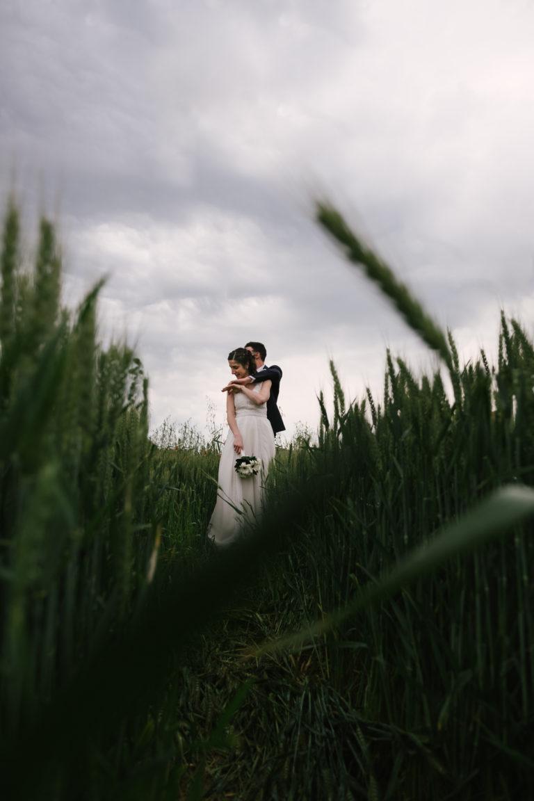 Due sposi che si abbracciano in un campo di grano